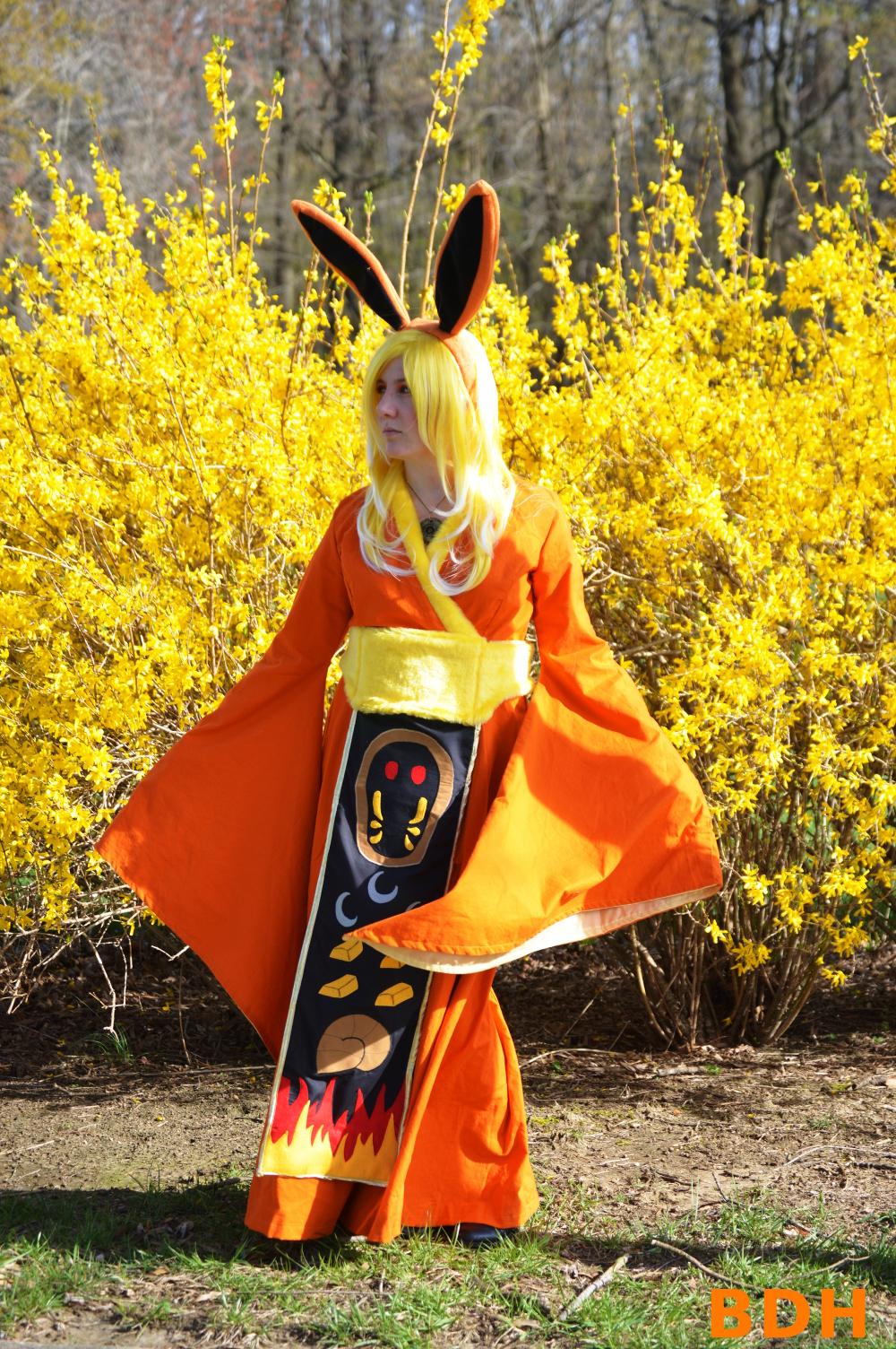 Flareon cosplay involving an orange gown with bell sleeves, long orange ears, and a banner depicting Kabuto and other TPP symbols.