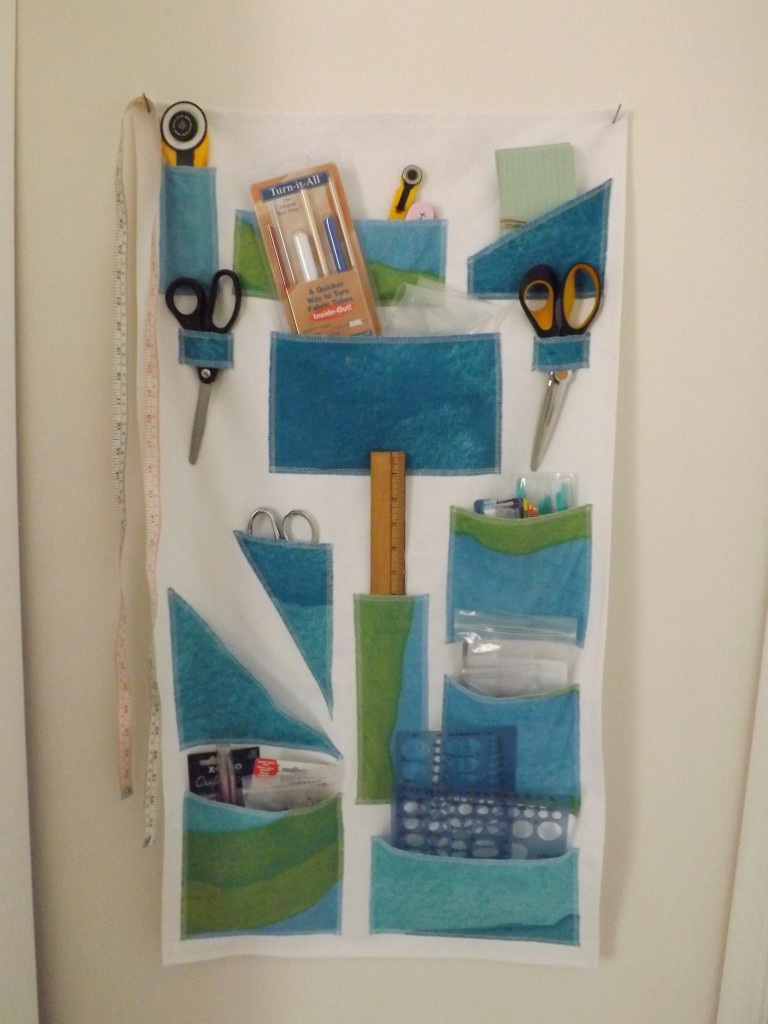 A photo of a white and blue fabric wall organizer.