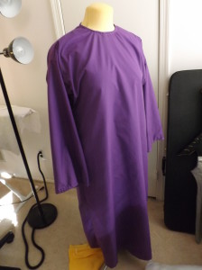 A purple robe hanging on a dress form.