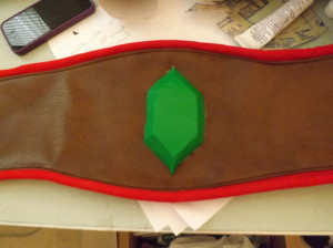 A photo of the center of a wide brown belt with red trim and a green rupee in the middle.