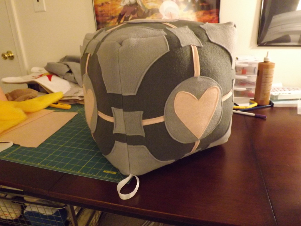 A photo of a big companion cube plush on my sewing table.