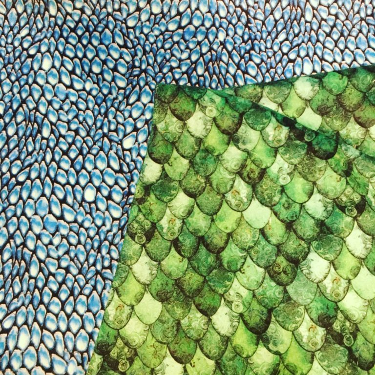 Image of two pieces of fabric, one light blue dragon scale print and one green mermaid scale print.