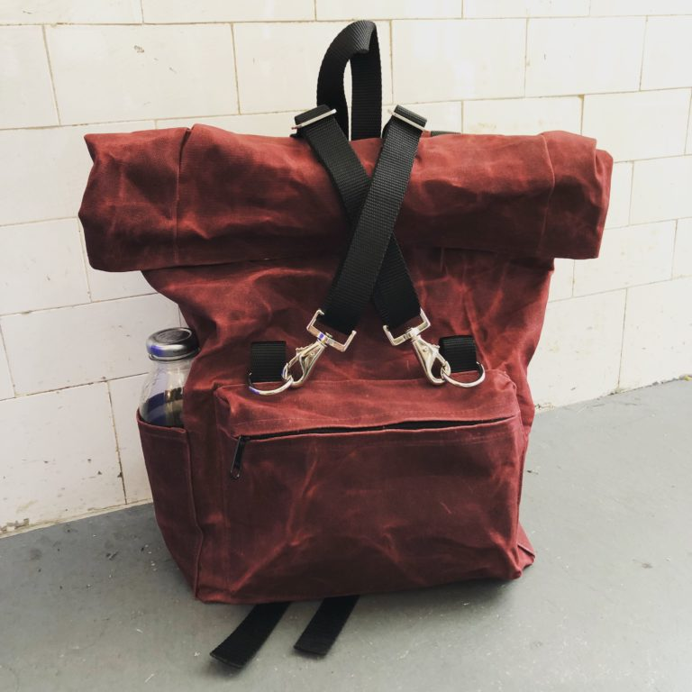 Burgundy waxed canvas roll-top backpack.