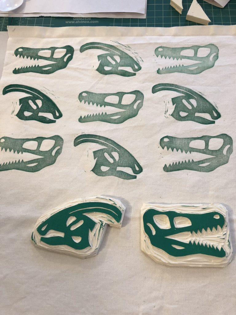 Hand-carved stamps of dinosaur skulls and the fabric they have printed.