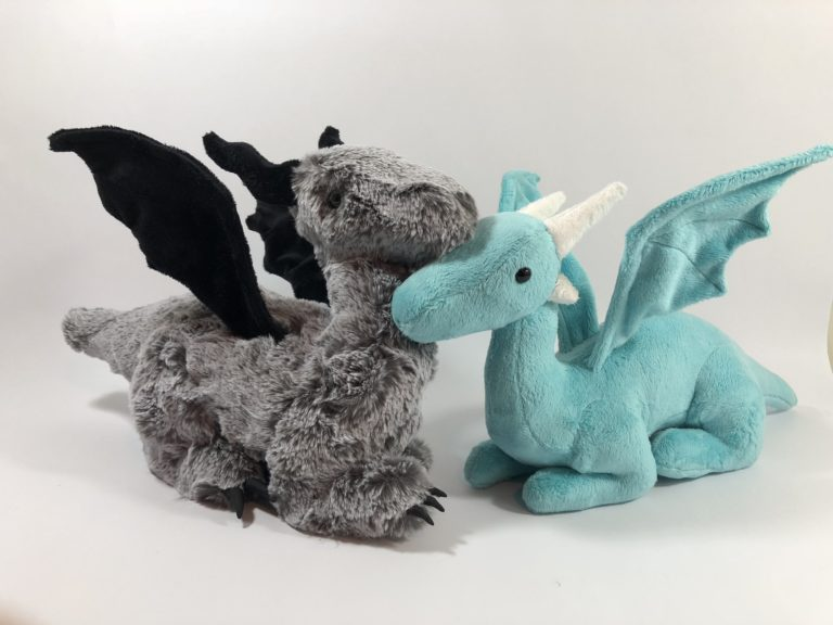 Photo of gray furry plush dragon and teal minky plush dragon rubbing noses.