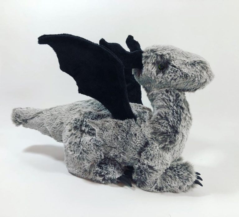 Dragon plush made of gray faux fur with black horns and wings.