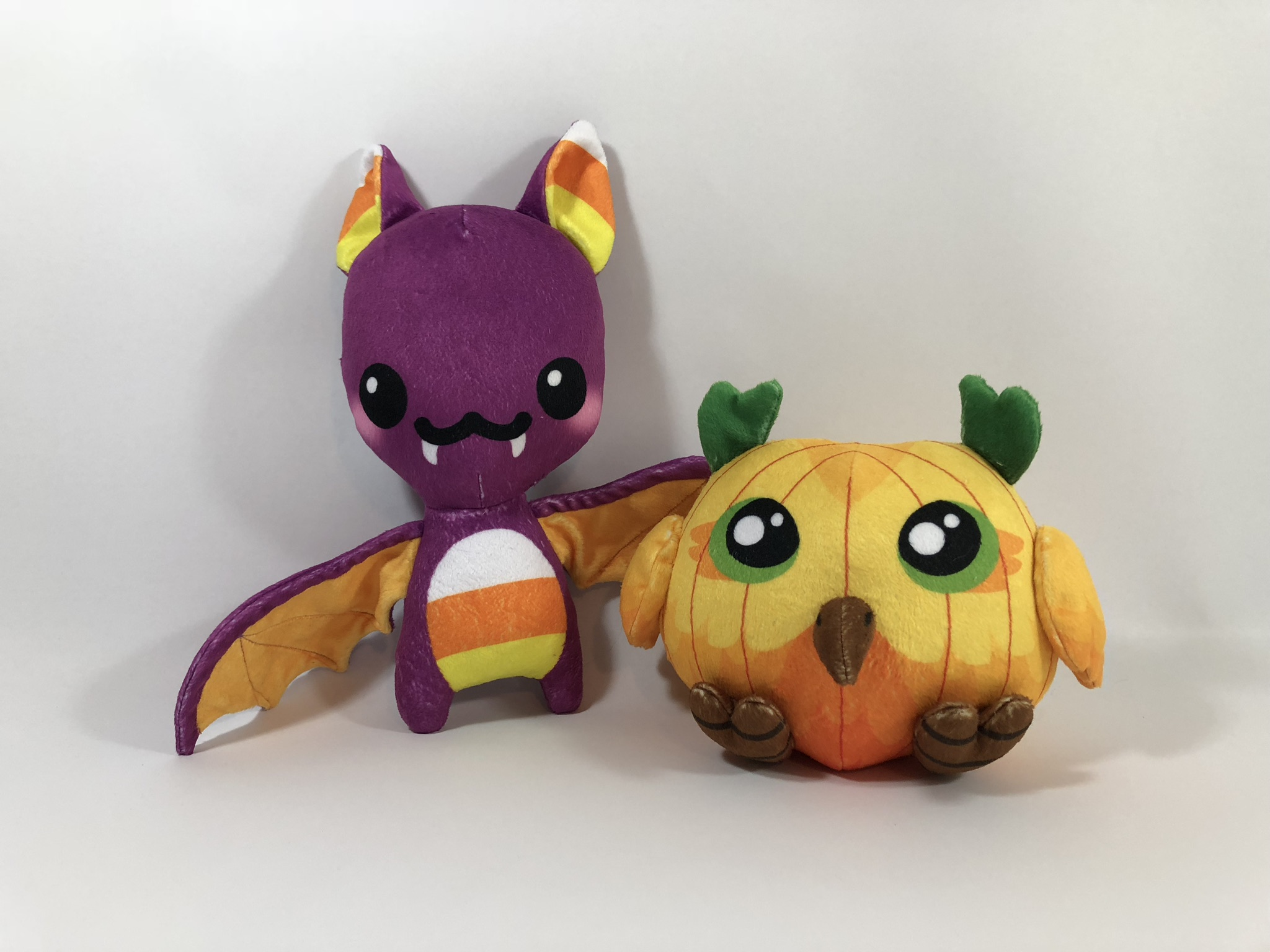 Purple and candy corn bat plush and an owl plush with a pumpkin design.