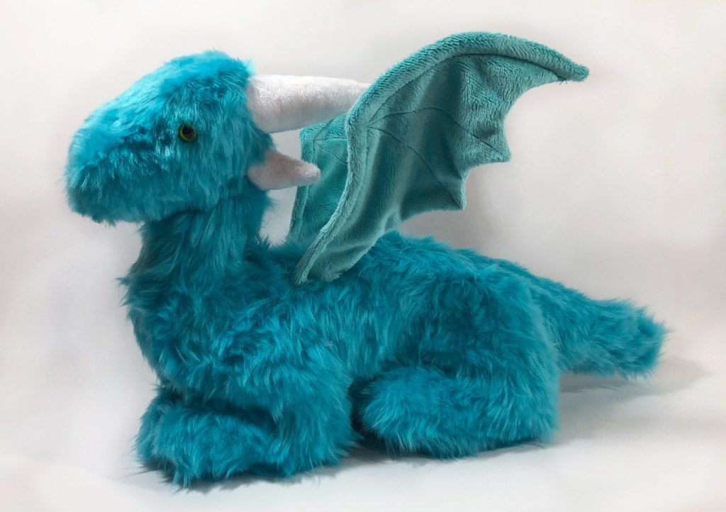 Photo of a teal, faux fur dragon plush with wired wings, as seen from the side. It is sitting down on four legs, with wings unfurled.