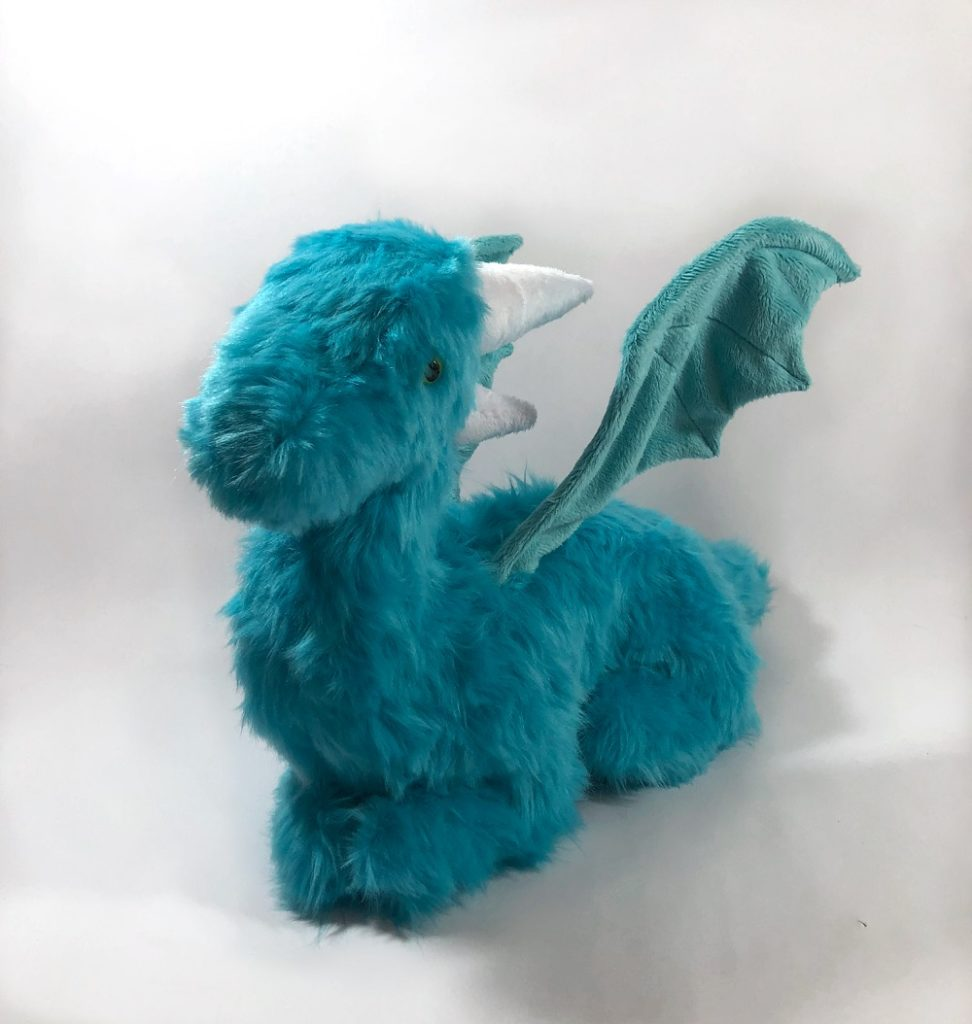 Teal, furry lush dragon seen from 3/4 view.