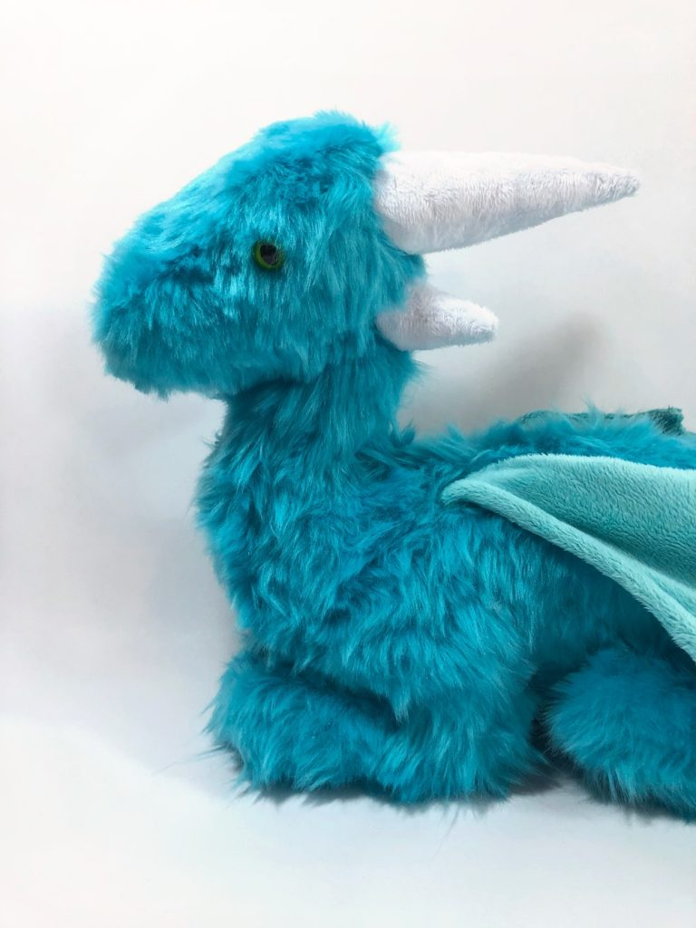 Closeup of the head and chest of the dragon plush. It has green safety eyes and white horns.