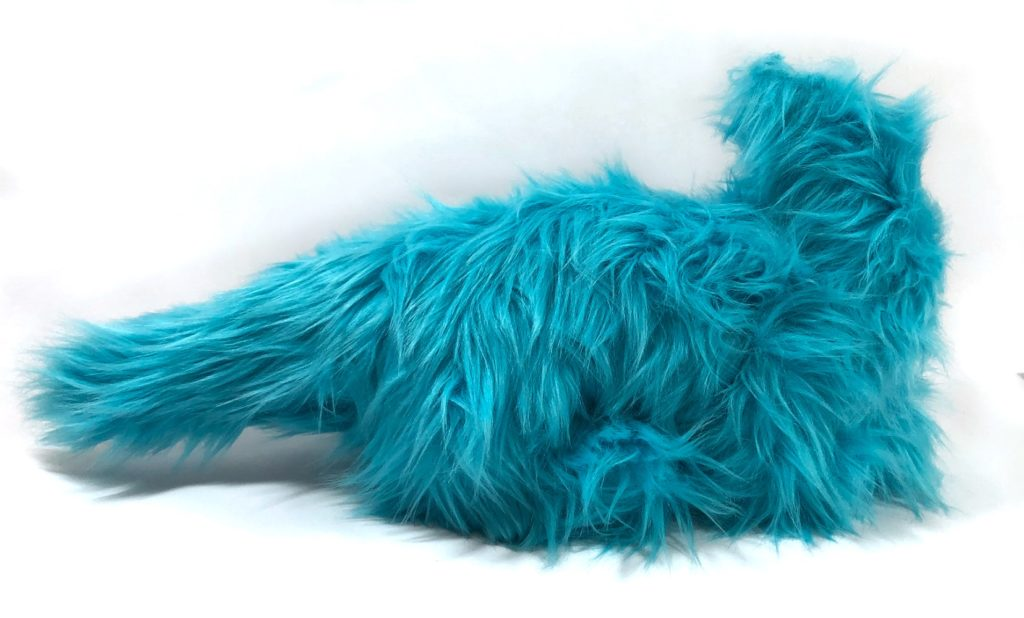 Photo of an unfinished dragon plush with long, shaggy fur. Front legs are not visible, and the back legs are barely visible. It does not yet have a head.