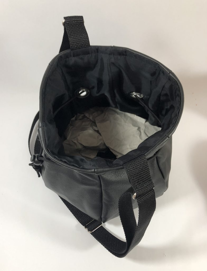 Top view of black leather drawstring bag. It is lined with satin-like black fabric.