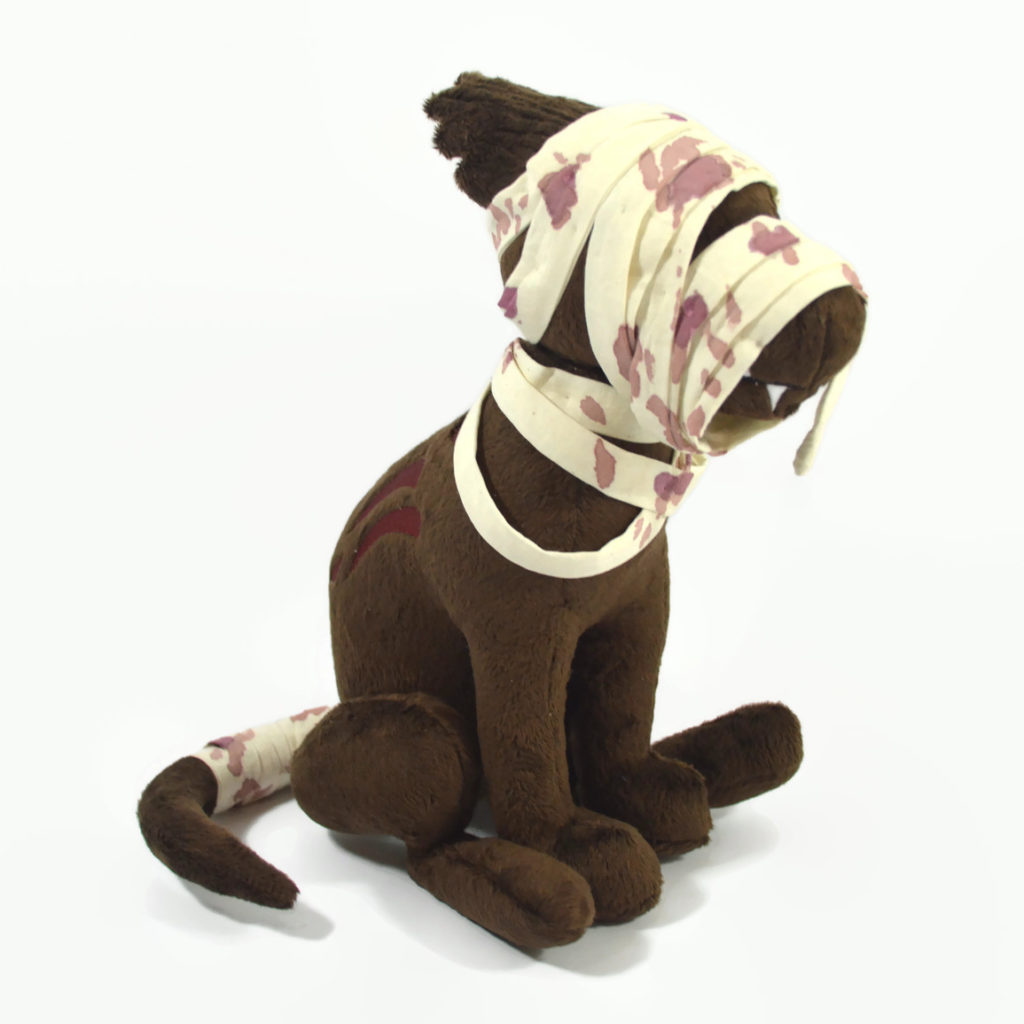 A brown zombie dog plush. It is sitting upright and has bloody bandages on its head, shoulders, and tail. It has red embroidered gashes in its side and jagged teeth are visible through the bandages on the muzzle.