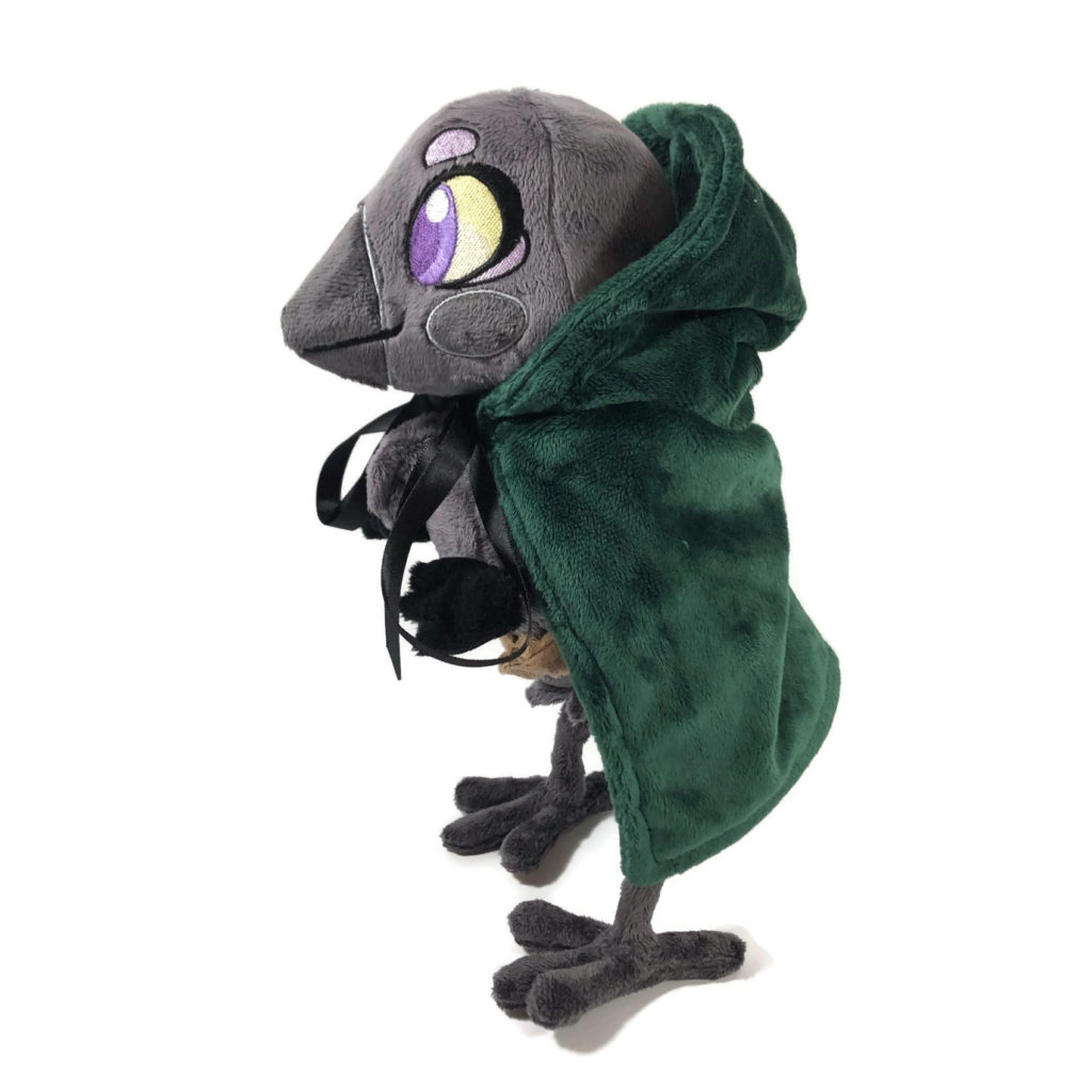 plush gray anthropomorphic crow with embroidered eyes and a green cloak