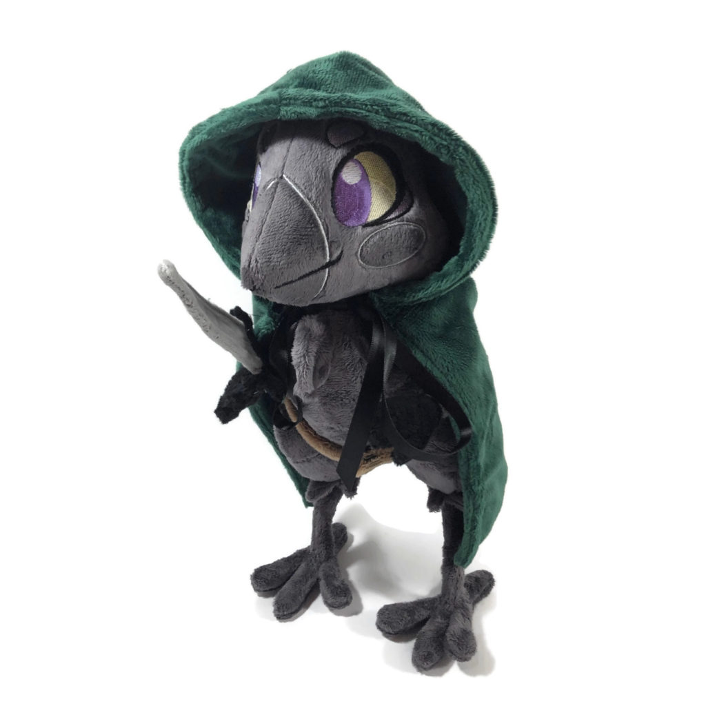 plush gray anthropomorphic crow with embroidered eyes and a green cloak, holding a fabric dagger