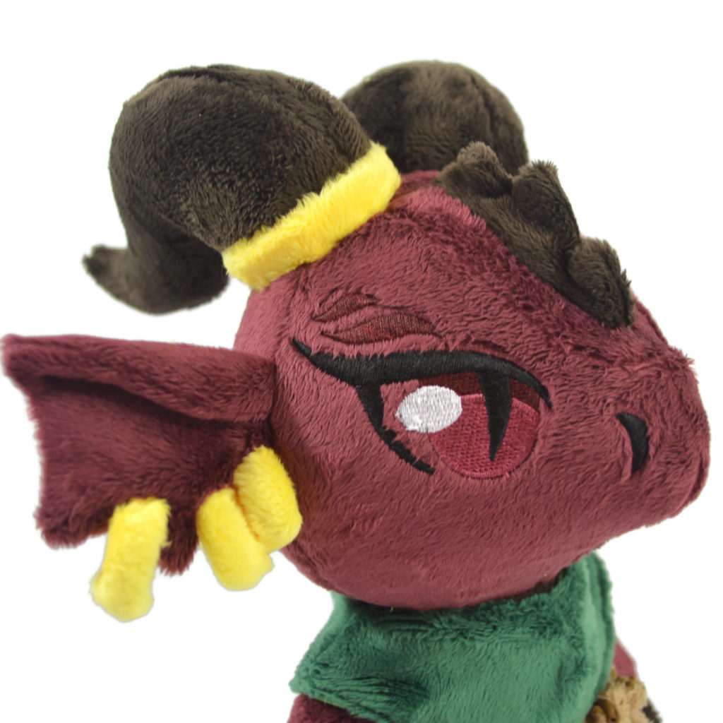 A close up photo of the red kobold's face. they have three gold earrings and a gold ring around one horn.