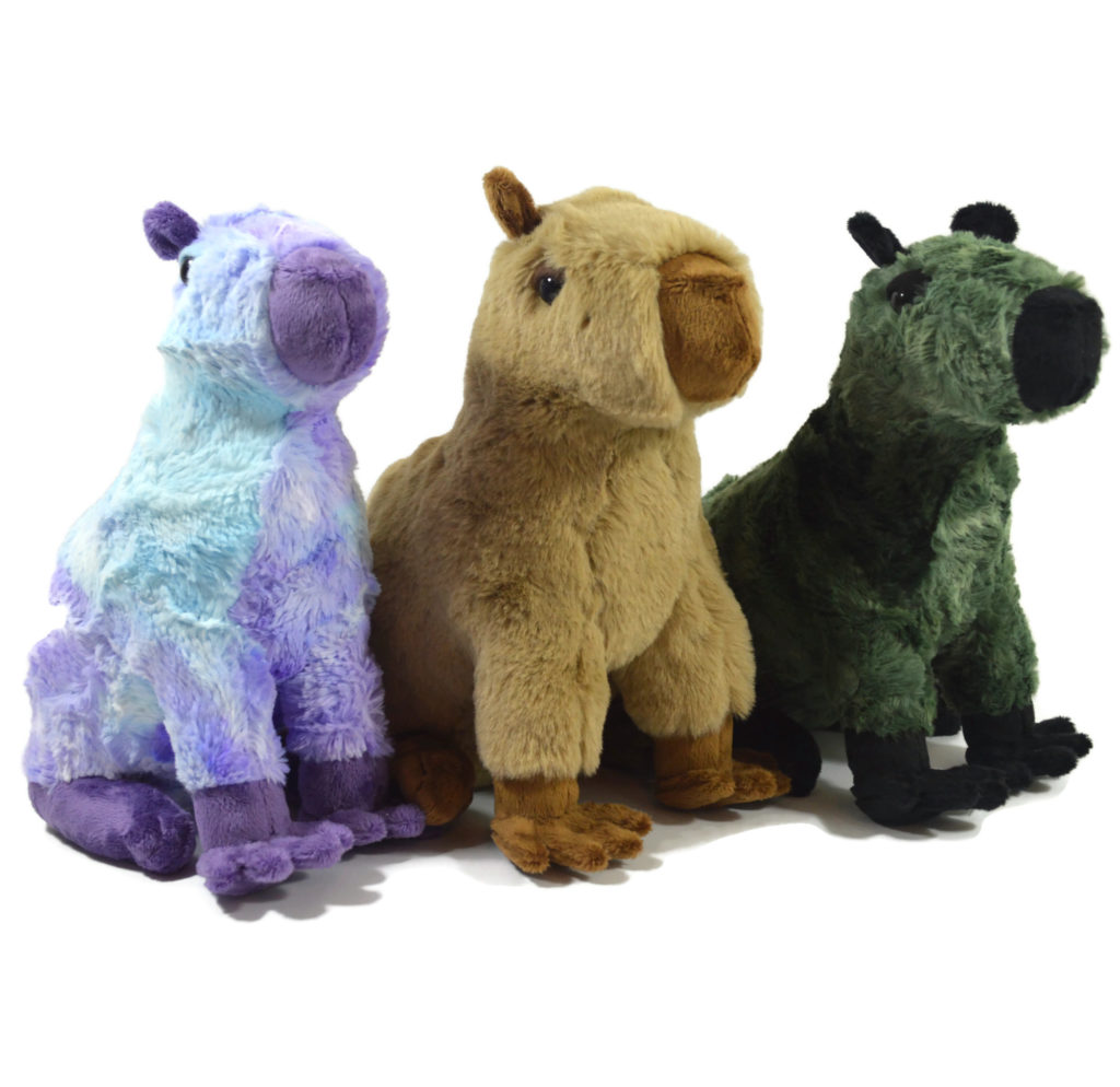 Three capybara plush in a row, with a purple and blue one on the left, a tan and brown one in the middle, and a green and black one on the right.